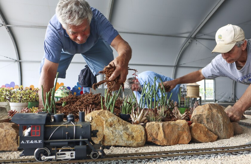 Claude Mueller, middle, Greg Ogrod and Andy Kann, from the San Diego Garden Railway Society set up for HomeGrownFun.