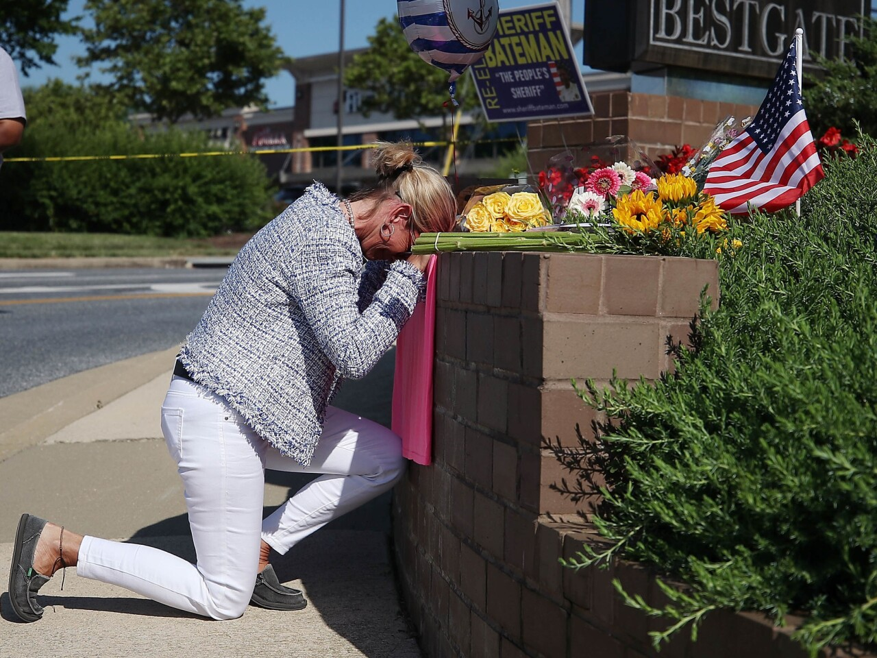 Lynne Griffin pays her respects at a makeshift memorial near the Capital newspaper offices, where five people were shot and killed Thursday in Annapolis, Md. Griffin was a journalism student under John McNamara, who was one of the people killed at the paper.