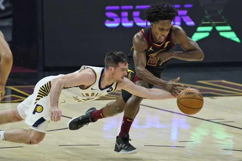 Indiana Pacers' T.J. McConnell, left, and Cleveland Cavaliers' Collin Sexton reach for the ball during the first half of an NBA basketball game Wednesday, March 3, 2021, in Cleveland. (AP Photo/Tony Dejak)