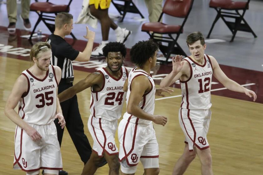 Oklahoma's Brady Manek (35), Elijah Harkless (24), Jalen Hill (1), and Austin Reaves (12) react during the second half of an NCAA college basketball game against Iowa State in Norman, Okla., Saturday, Feb. 6, 2021. Oklahoma won 79-72. (AP Photo/Garett Fisbeck)