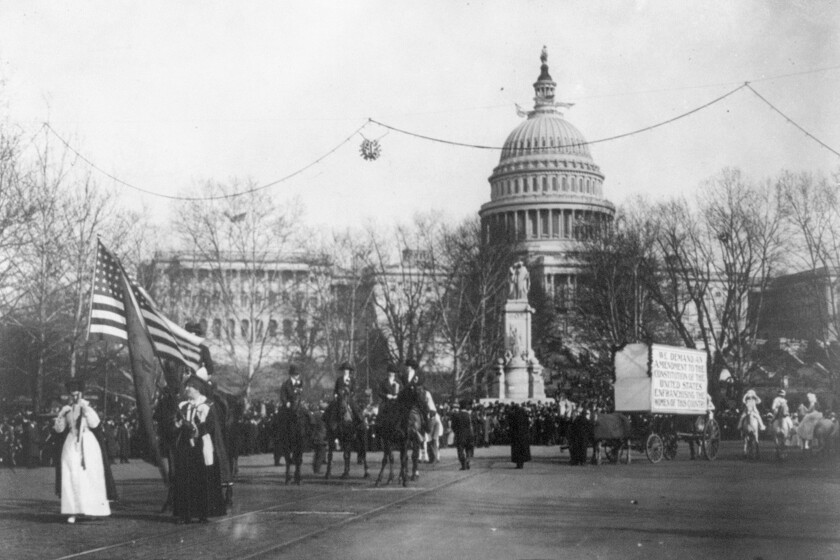 Demonstrators march in a women's suffrage parade near the Capitol building in Washington, D.C., circa 1913.