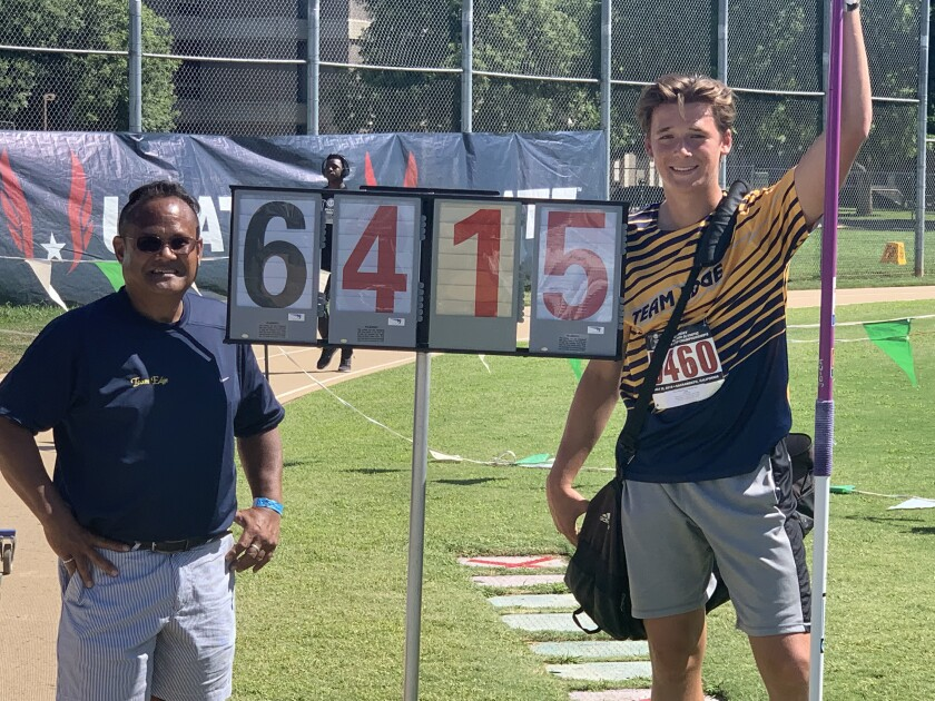 Coach Erl Cabanas and Chris White standing by his winning mark on the field just after the event finished.