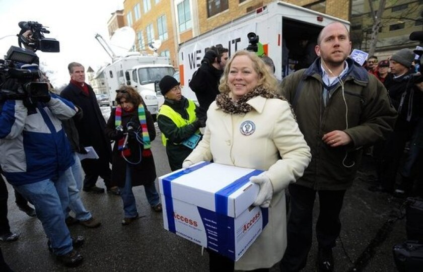 In Madison, United Wisconsin leader Julie Wells delivers the first of many boxes of petitions containing signatures to force a recall election of Wisconsin Gov. Scott Walker, a Republican.