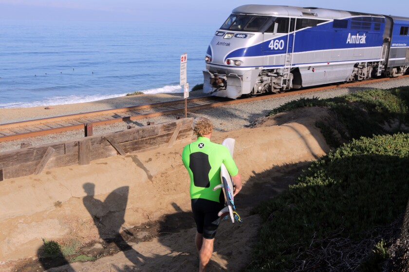 An Amtrak train heads south in Del Mar as a surfer approaches the tracks.