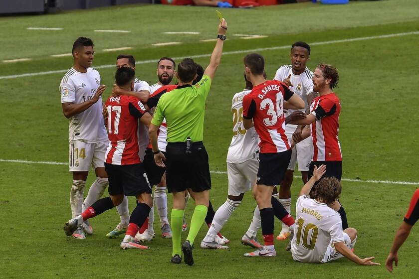 Jugadores del Athletic Bilbao y Real Madrid forcejean durante el partido de la Liga de España en Bilbao
