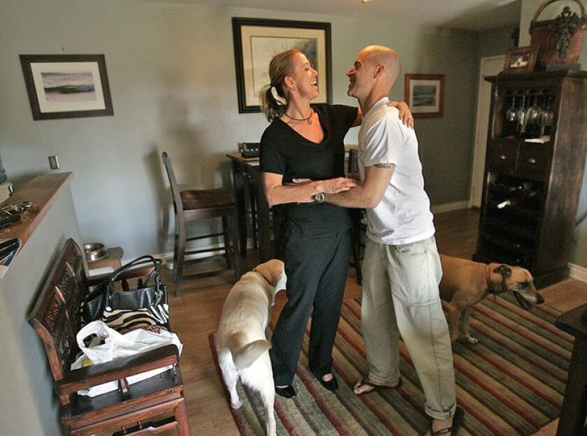 """Tim Salmon hugged his wife, Leah Salmon, in their Carlsbad home. The couple are scrambling to pay for his $7,000-a-month prescription drug for multiple sclerosis because her insurance won't cover it. """"A generic drug really would have helped me bridge that gap,"""" he said. (John Gastaldo /"""