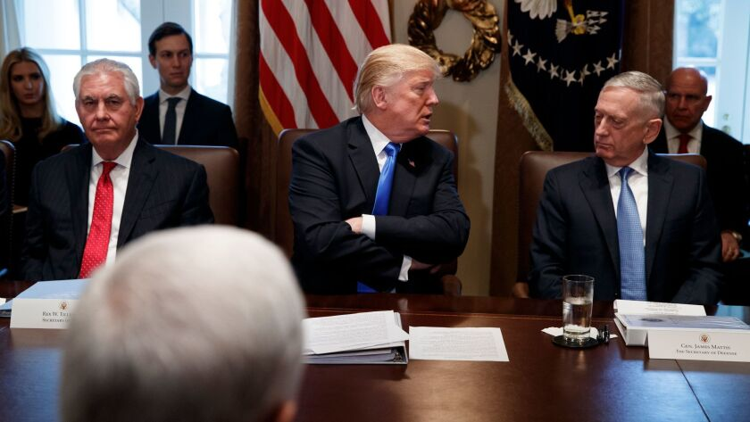 Secretary of State Rex Tillerson, left, and Secretary of Defense Jim Mattis, right, listen as President Donald Trump speaks during a cabinet meeting at the White House on Dec. 20.