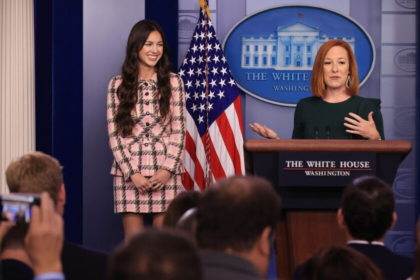 A woman in a dark dress, right, standing at a White House lectern, gestures next to a smiling young woman with dark hair
