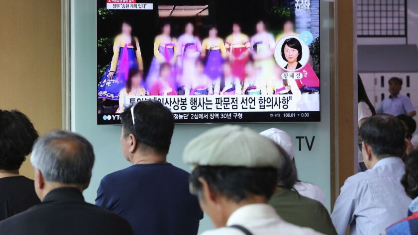 A TV screen shows a blurred photo of North Korean restaurant workers in China, during a news program