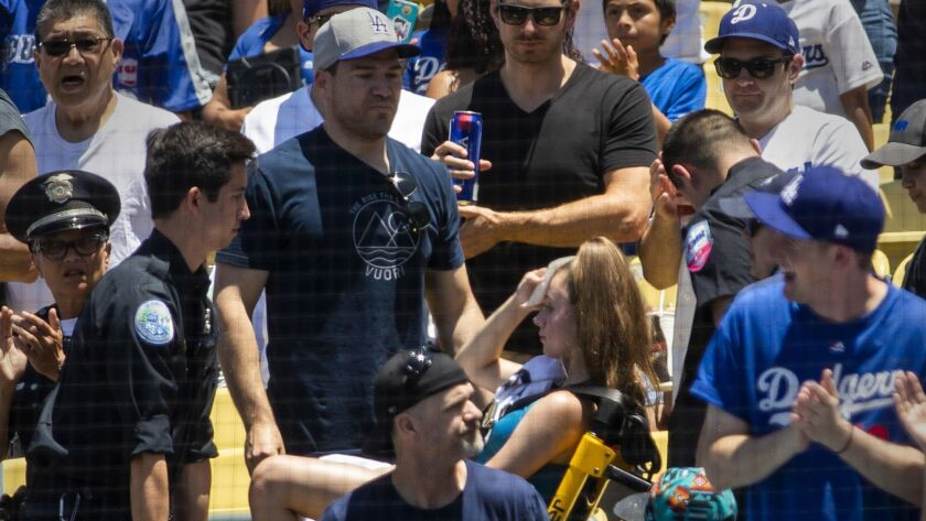A young fan is given medical attention after being struck with a foul ball hit by Dodgers outfielder Cody Bellinger during the first inning Sunday.