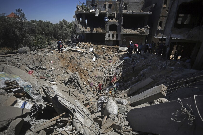 Palestinians inspect the damage of a destroyed house that was hit by an Israeli airstrike in town of Khan Younis, southern Gaza Strip, Wednesday, May 19, 2021. (AP Photo/Yousef Masoud)