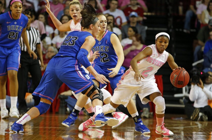 North Carolina State's Len'Nique Brown-Hoskin (2) tries to avoid Duke's Mercedes Riggs (12) and Rebecca Greenwell (23) during the first half of an NCAA college basketball game, Sunday, Feb. 22, 2015, in Raleigh, N.C. (AP Photo/Karl B DeBlaker)