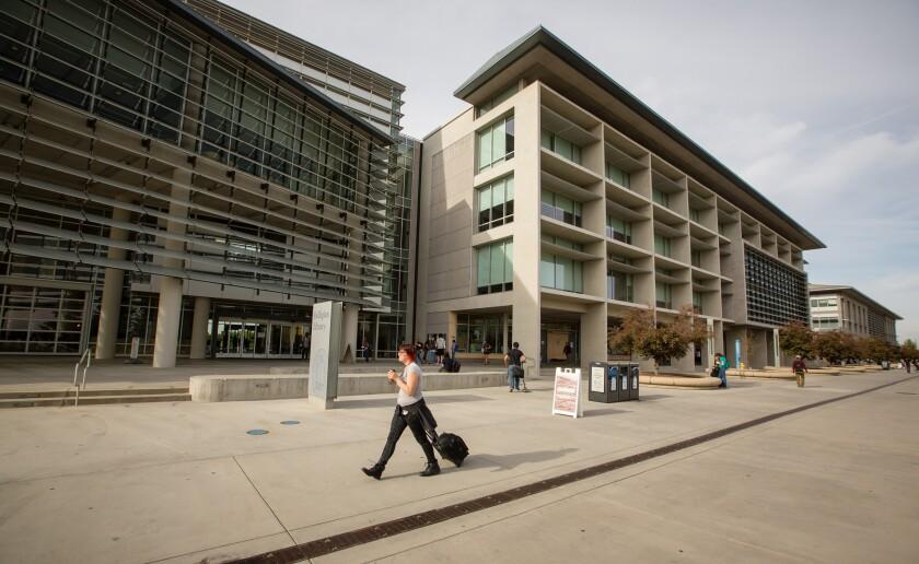 Passersby walk UC Merced's campus