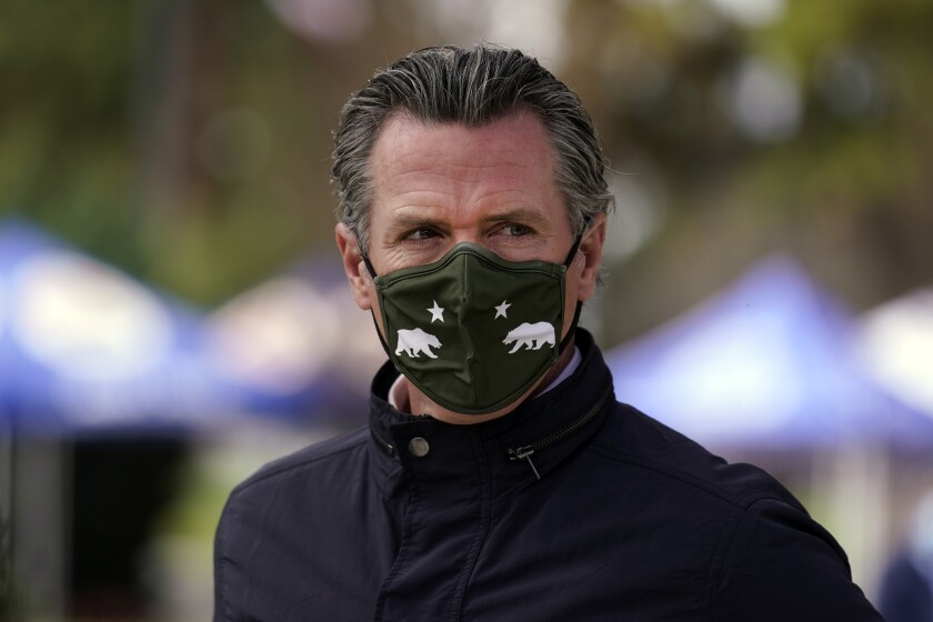 A closeup of Gavin Newsom in a mask with California flag insignia.