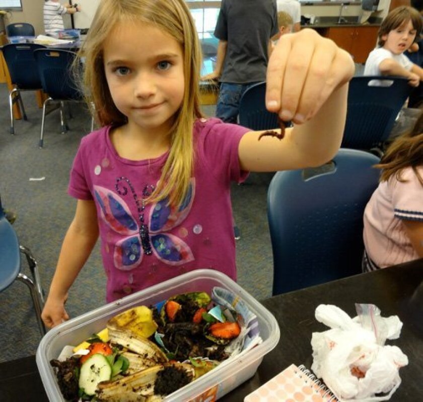 Ranch School students learn by doing. First grader Joani Berger tries her hand at composting.