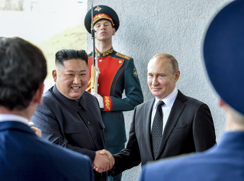 Russian President Vladimir Putin and North Korea's leader Kim Jong Un shake hands during their meeting in Vladivostok, Russia, on Thursday. Putin and Kim are set to have a one-on-one meeting at the Far Eastern State University.