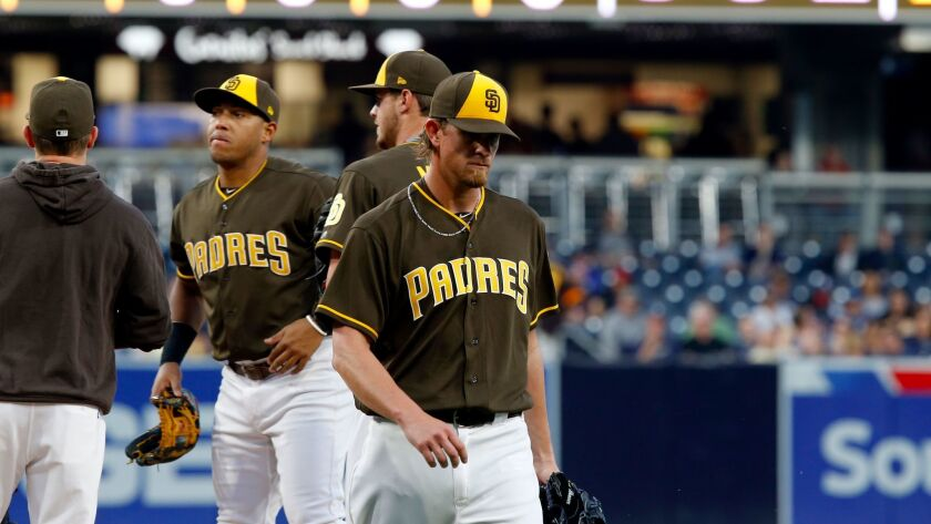 San Diego Padres starting pitcher Jered Weaver, right, walks away, as manager Andy Green, left, with