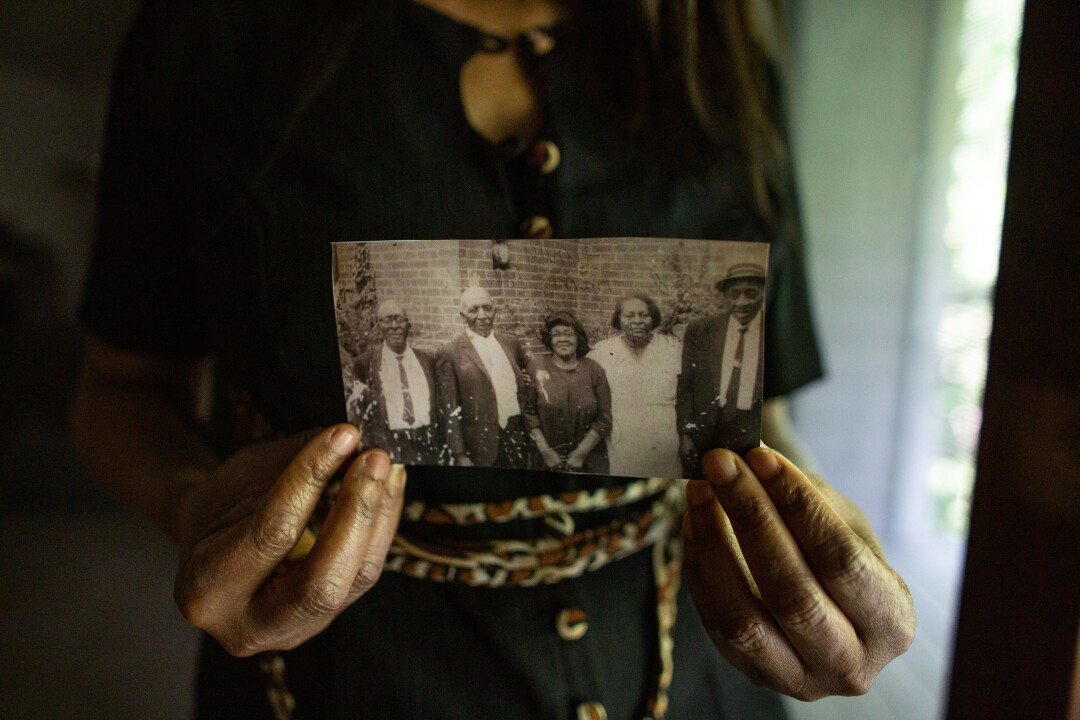Angela Harrelson holds a photo of  George Floyd's great-grandparents and other relatives.