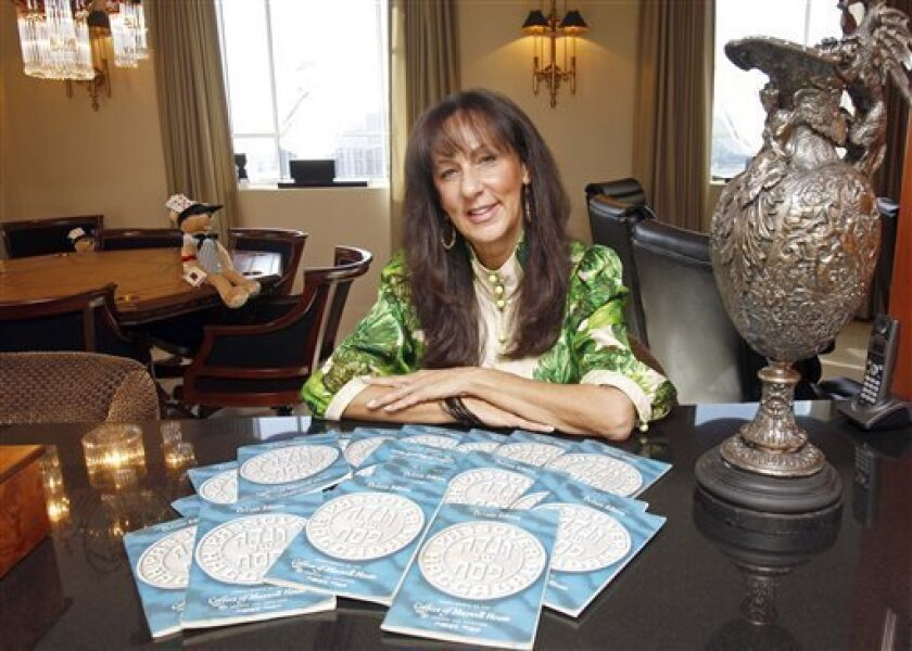 This March 11, 2011 photo shows Susan Schein at her home in Sunny Isles Beach, Fla., with her collection of Maxwell House Haggadahs from 1965 that her father had given her when she started her own family and hosted her first Passover. Susan still uses them today. The coffee maker's version of th