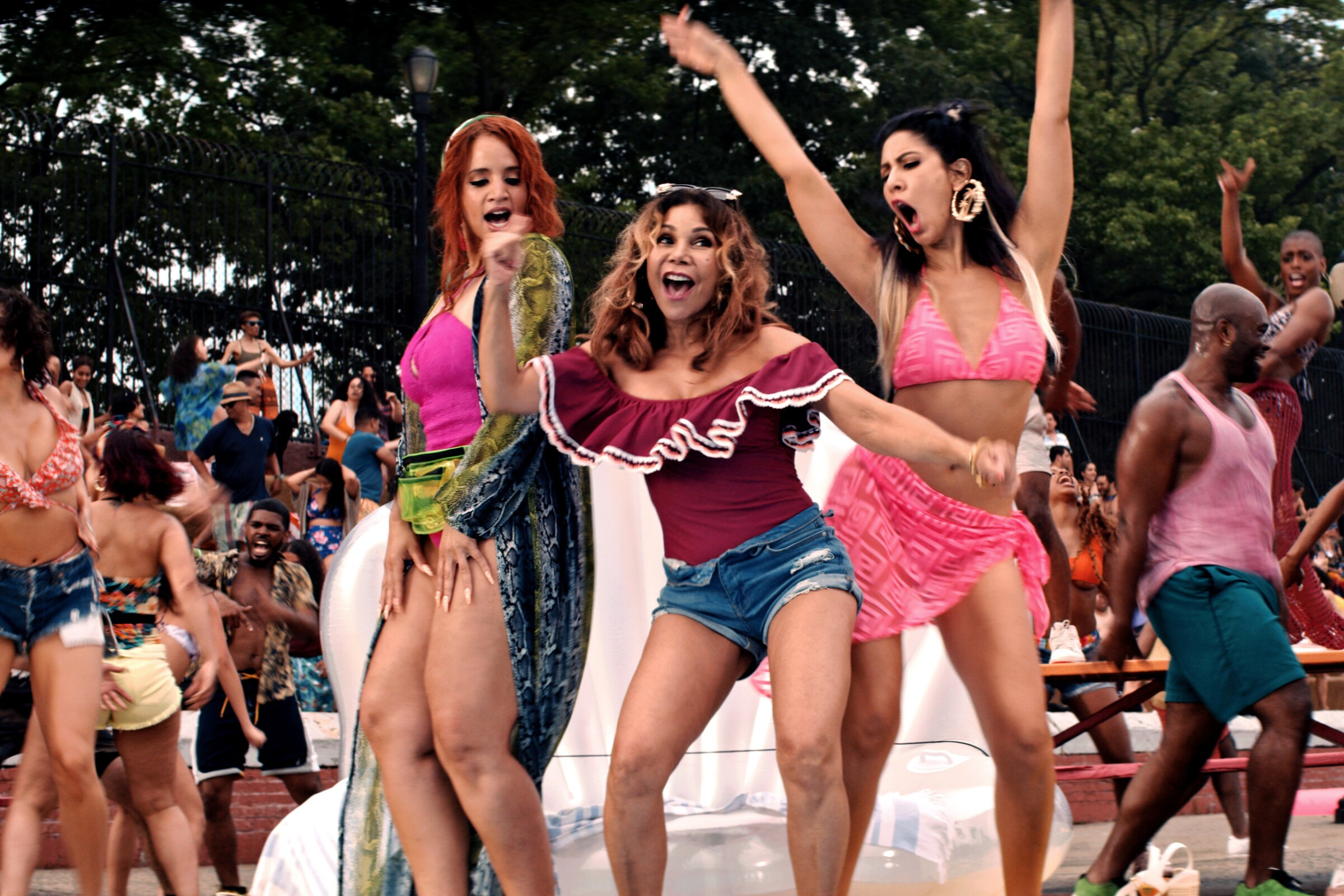 """A scene from """"In the Heights"""" shows people dancing on a pool deck."""