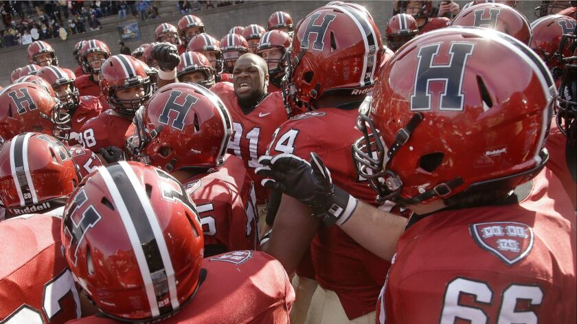 Members of the Harvard football team prepare to take the field in an NCAA game in Cambridge, Mass. on Nov. 22, 2014.