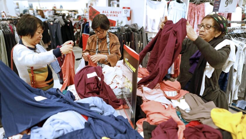 Shoppers rummage through tops on Black Friday at JCPenney at the Glendale Galleria.