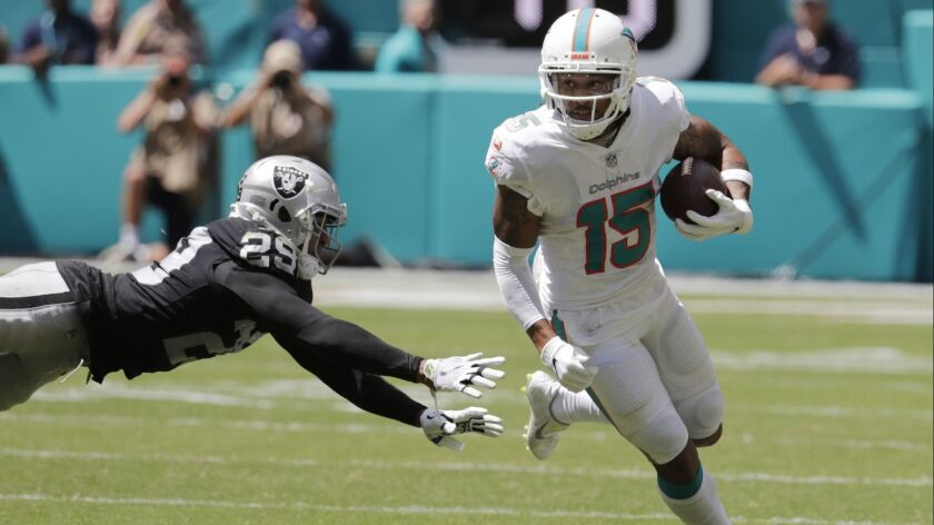 Dolphins receiver Albert Wilson eludes Raiders defensive back Leon Hall during the first half Sunday.