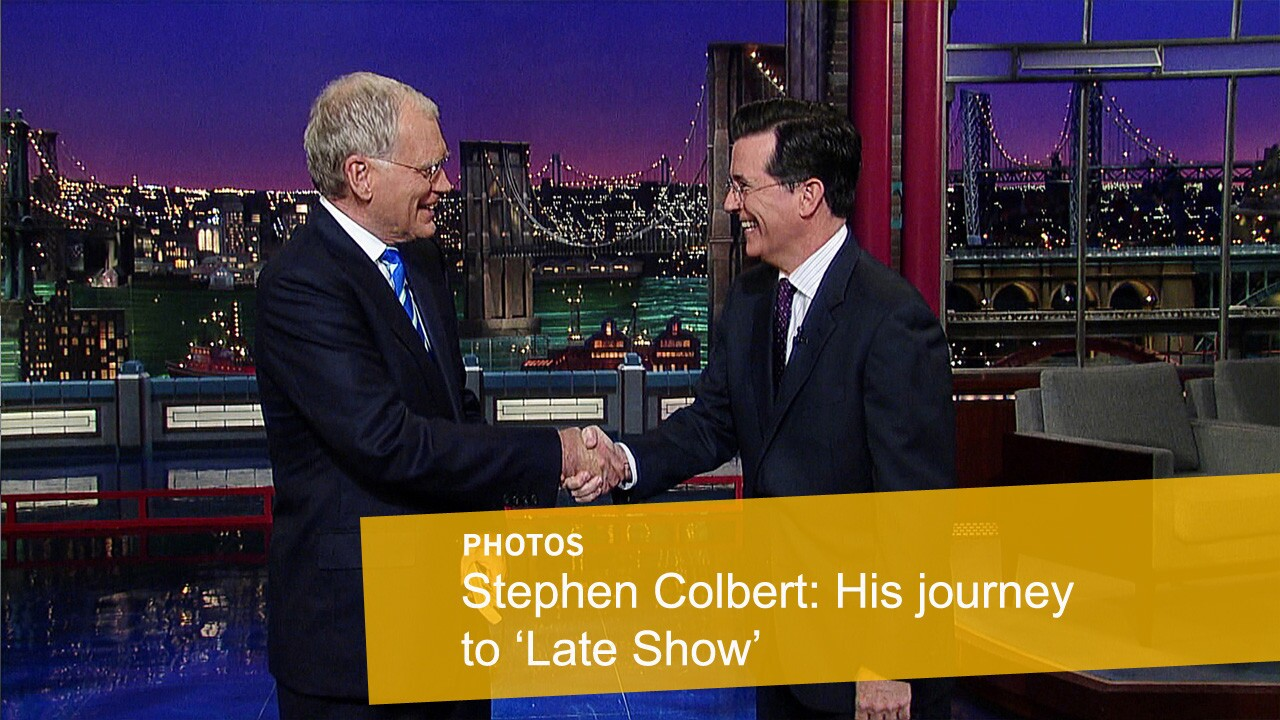 """Stephen Colbert has been named as the successor to David Letterman as host of """"The Late Show."""" Above, Letterman shakes hands with Colbert after Colbert came by for a surprise visit in 2011."""