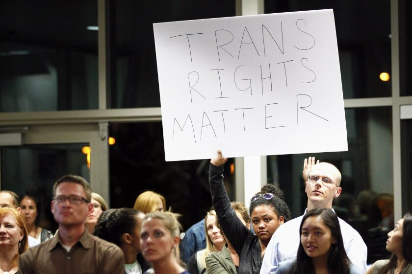 Morgan Smith, a senior at Francis Parker High School, holds a sign in favor of a transgender student's use of the boys locker room at RB High as she and an overflow crowd watch a Poway Unified School District board meeting from the lobby in San Diego on Tuesday.