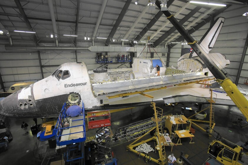 The payload bay doors of the space shuttle Endeavour, housed at the California Science Center, stand open for the installation of equipment.