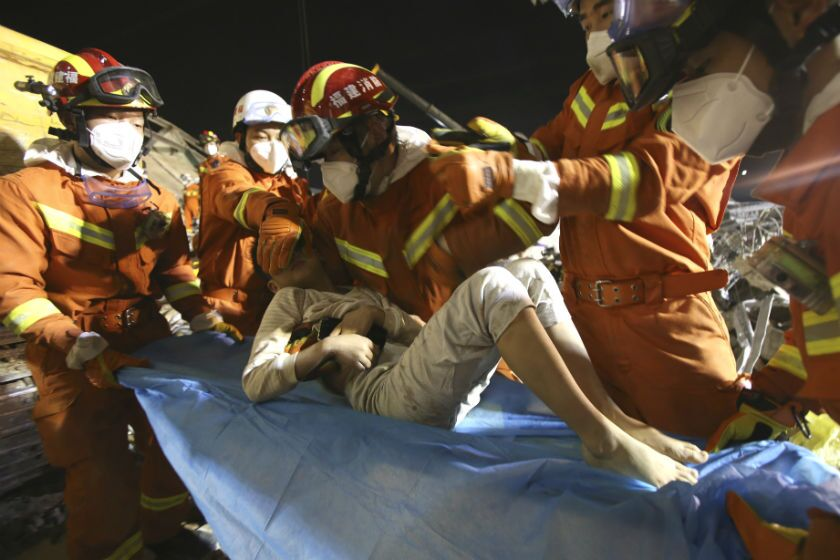 Rescuers treat a boy who was pulled from the rubble of a collapsed hotel in Quanzhou, China