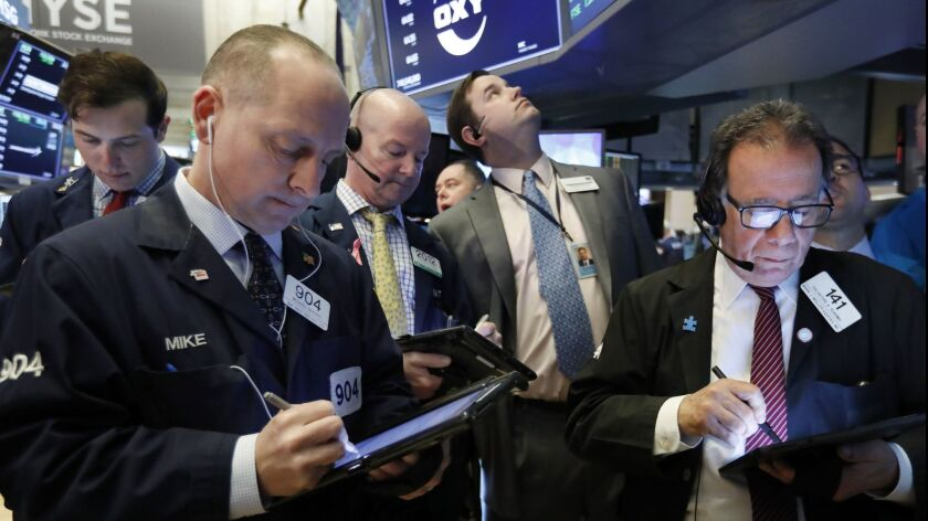 Traders gather at the post that handles Oaktree Capital Group on the floor of the New York Stock Exc