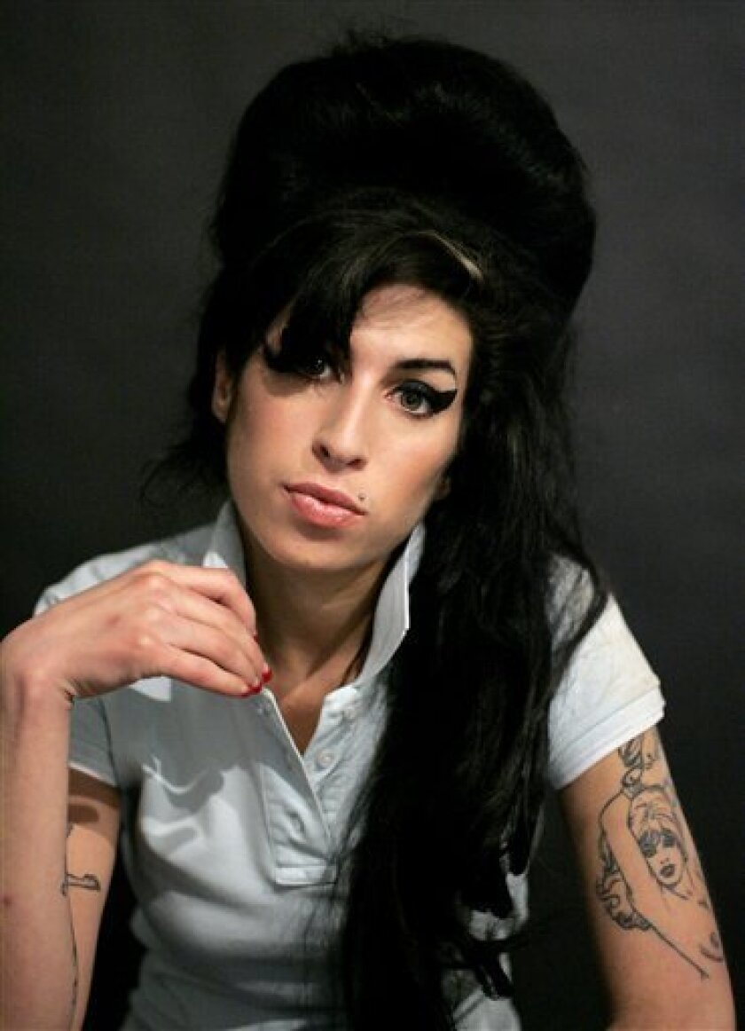 FILE - In this Friday Feb. 16, 2007 file photo British singer Amy Winehouse poses for photographs after being interviewed by the Associated Press at a studio in north London. British officials say the coroner who oversaw the inquest into the death of singer Amy Winehouse has resigned after her qualifications were questioned. Winehouse's relatives said they were still absorbing the implications of the news. In October, coroner Suzanne Greenaway ruled that the soul singer had died from accidental alcohol poisoning. (AP Photo/Matt Dunham, File)
