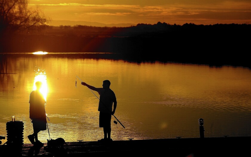 Two men fish from a dock in the delta near Stockton. State officials are more confident that there was enough water in reservoirs to meet human health and safety needs and provide some supplies for senior rights holders in the Sacramento and San Joaquin valleys.