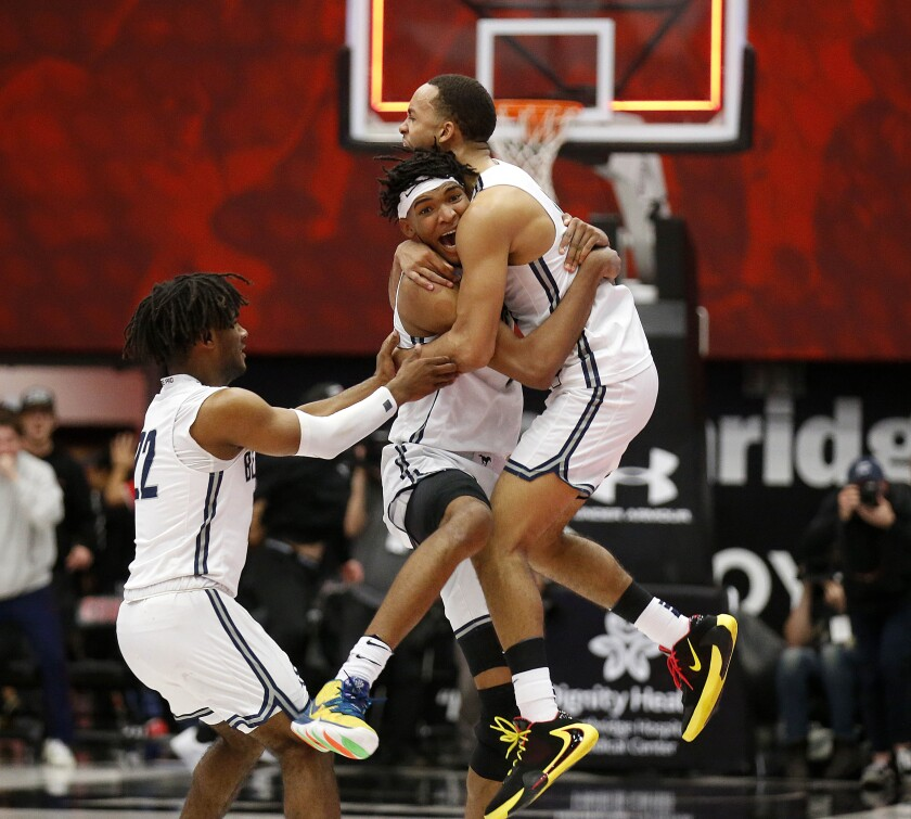 Ziaire Williams, with headband, celebrates with Sierra Canyon teammates Amari Bailey, right, and Tookey Wigington (22) after making the game-winning basket as time expired against Etiwanda in the Southern California Open Division final on March 10 at Cal State Northridge.