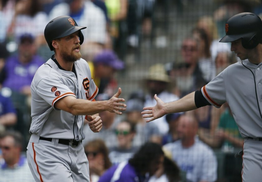 San Francisco Giants' Hunter Pence, left, is congratulated by Buster Posey after the pair scored on a double hit by Brandon Belt off Colorado Rockies starting pitcher Chris Rusin in the third inning of a baseball game Sunday, May 29, 2016, in Denver. (AP Photo/David Zalubowski)