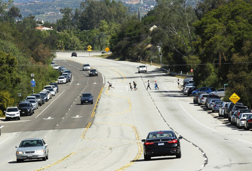 People cross State Route 67 near Mt. Woodson, a popular hiking area.