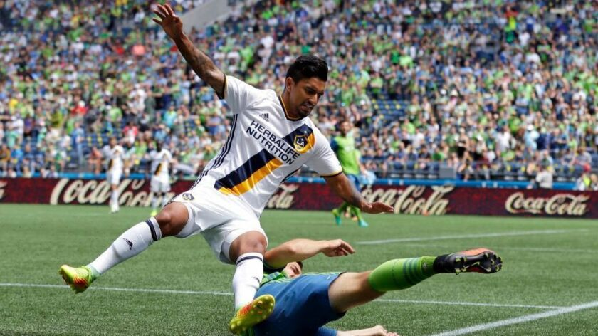 Galaxy defender A.J. DeLaGarza goes down on a tackle by Sounders midfielder Jordan Morris during the first half of a game in Seattle on July 31.