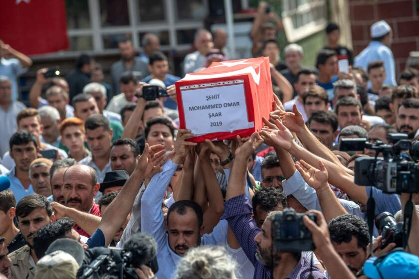 An infant's coffin is carried in Akcakale.