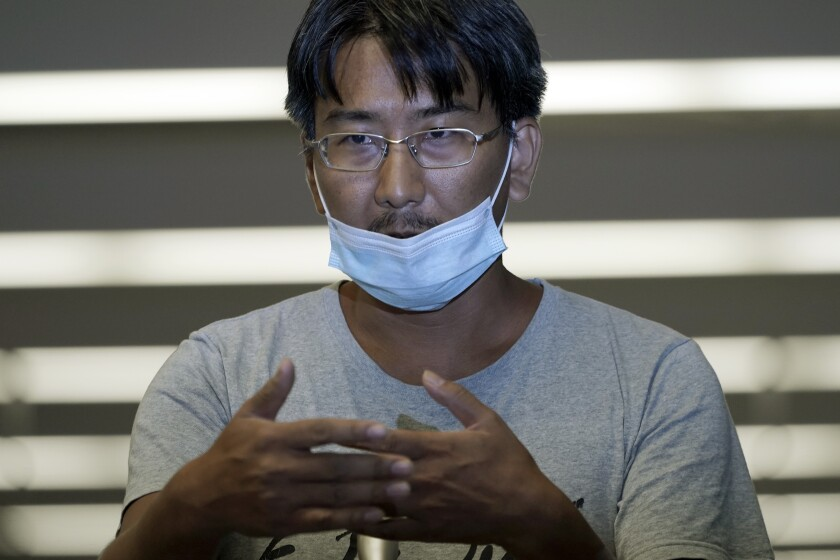 Yuki Kitazumi, a Japanese freelance journalist detained by security forces in Myanmar in mid-April and accused of spreading fake news criticizing the military coup gestures to speak upon his arrival at Narita International Airport, in Narita, east of Tokyo. (AP Photo/Eugene Hoshiko)