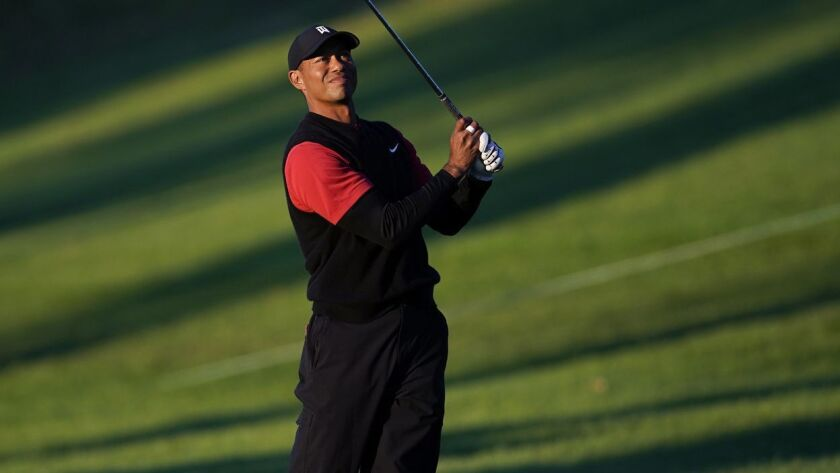 Tiger Woods hits his second shot on the 18th hole as third round play continues during the Genesis O