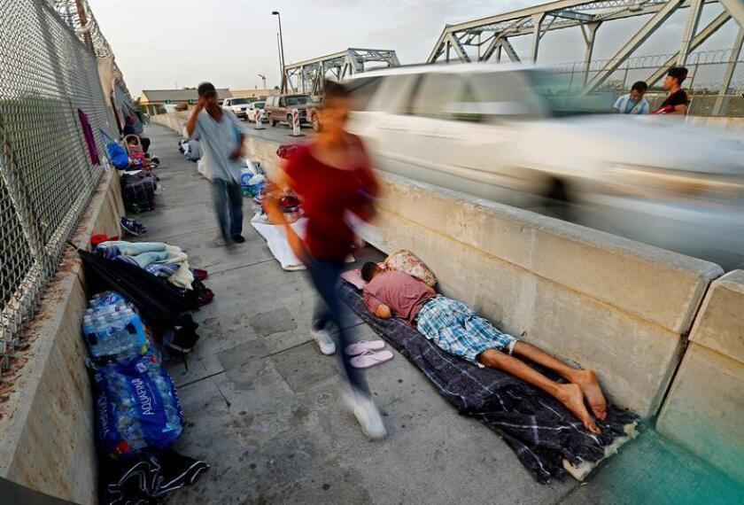 Varias personas que se dirigen a cruzar la frontera pasan junto a varios solicitantes de asilo de Guatemala y Cuba que aguardan para poder entrar EE.UU. cerca de la frontera en Matamoros (México). EFE/Archivo