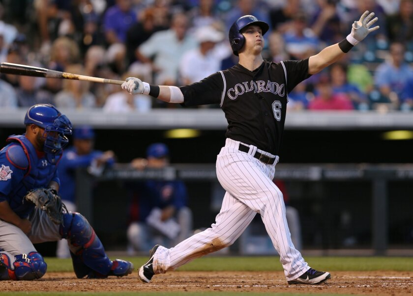 Colorado Rockies' Corey Dickerson, right, swings at a pitch as Chicago Cubs catcher Wellington Castillo fields the ball in the fourth inning of a baseball game in Denver on Wednesday, Aug. 6, 2014. Dickerson went on to hit an RBI-triple in the appearance at the plate. (AP Photo/David Zalubowski)