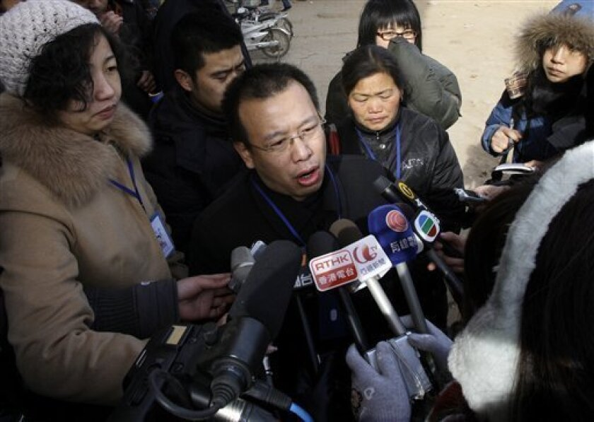 FILE - In this Jan. 22, 2009 file photo, Zhao Lianhai, center, the father of a boy sickened after he drank tainted milk formula, speaks to journalists outside the Intermediate People's Court in Shijiazhuang, in China's Hebei province. Zhao, the Chinese man who organized a support group for parents of children sickened in one of the country's worst food safety scandals was found guilty of inciting social disorder and sentenced Wednesday, Nov. 10, 2010, to 2 1/2 years in prison, his lawyer said. (AP Photo/Greg Baker, File)