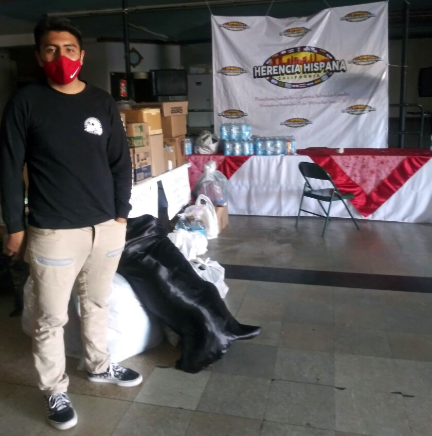 Un voluntario organiza donaciones que ha recibido Herencia Hispana California.