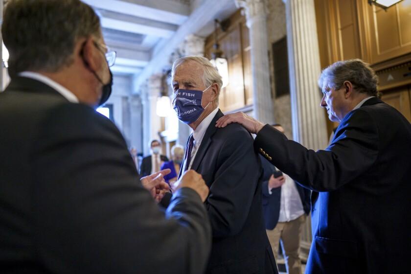 El senador independiente Angus King, al centro, habla con su colega demócrata Gary Peters, izquierda