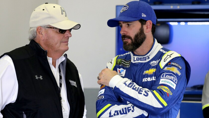 NASCAR driver Jimmie Johnson talks to team owner Rick Hendrick in their garage during a practice session at Daytona International Speedway on Friday.