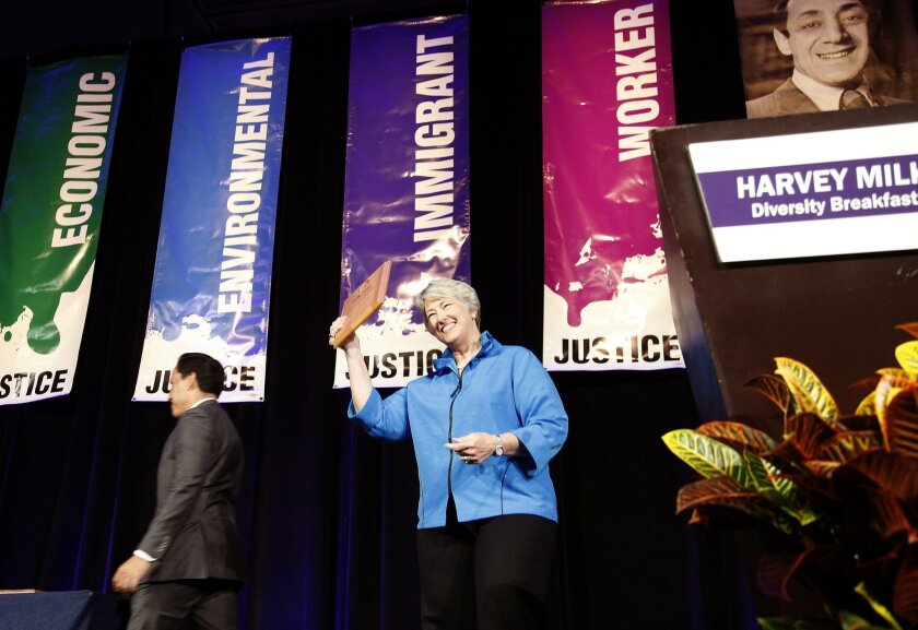 Hon. Annise Parker, former Mayor of Houston, looks back at the crowd after receiving the Harvey Milk Lifetime Achievement Award presented to her by San Diego City Councilman Todd Gloria, at left.
