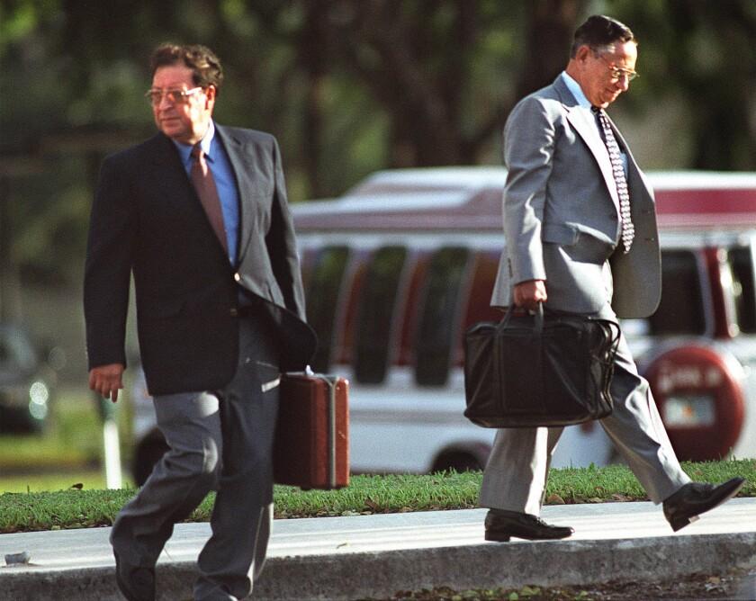 Carlos Vides Casanova (izquierda) y José Guillermo García, generales retirados de El Salvador, al salir de una corte federal en Florida.
