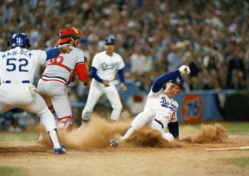 Dodgers pitcher Orel Hershiser slides across home plate in the second inning of Game 2 of the NLCS.